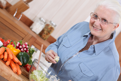 Aging woman in kitchen preparing salad