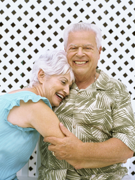 Close-up of a senior couple standing near a fence