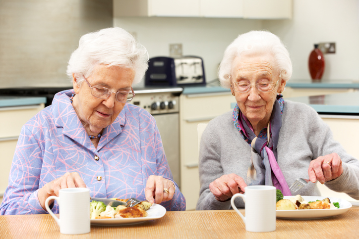 Senior friends enjoying meal in kitchen