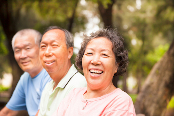 Three Asian seniors smiling in a park