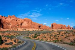 A lonely road winds through Arches National Park in UT (Utah)