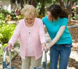 Elderly woman with walker receiving assisted care from aide