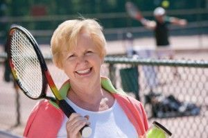 Mature woman playing tennis at her retirement home
