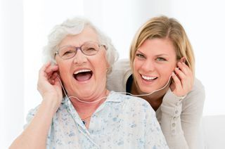 A senior and caregiver share headphones while enjoying a song together